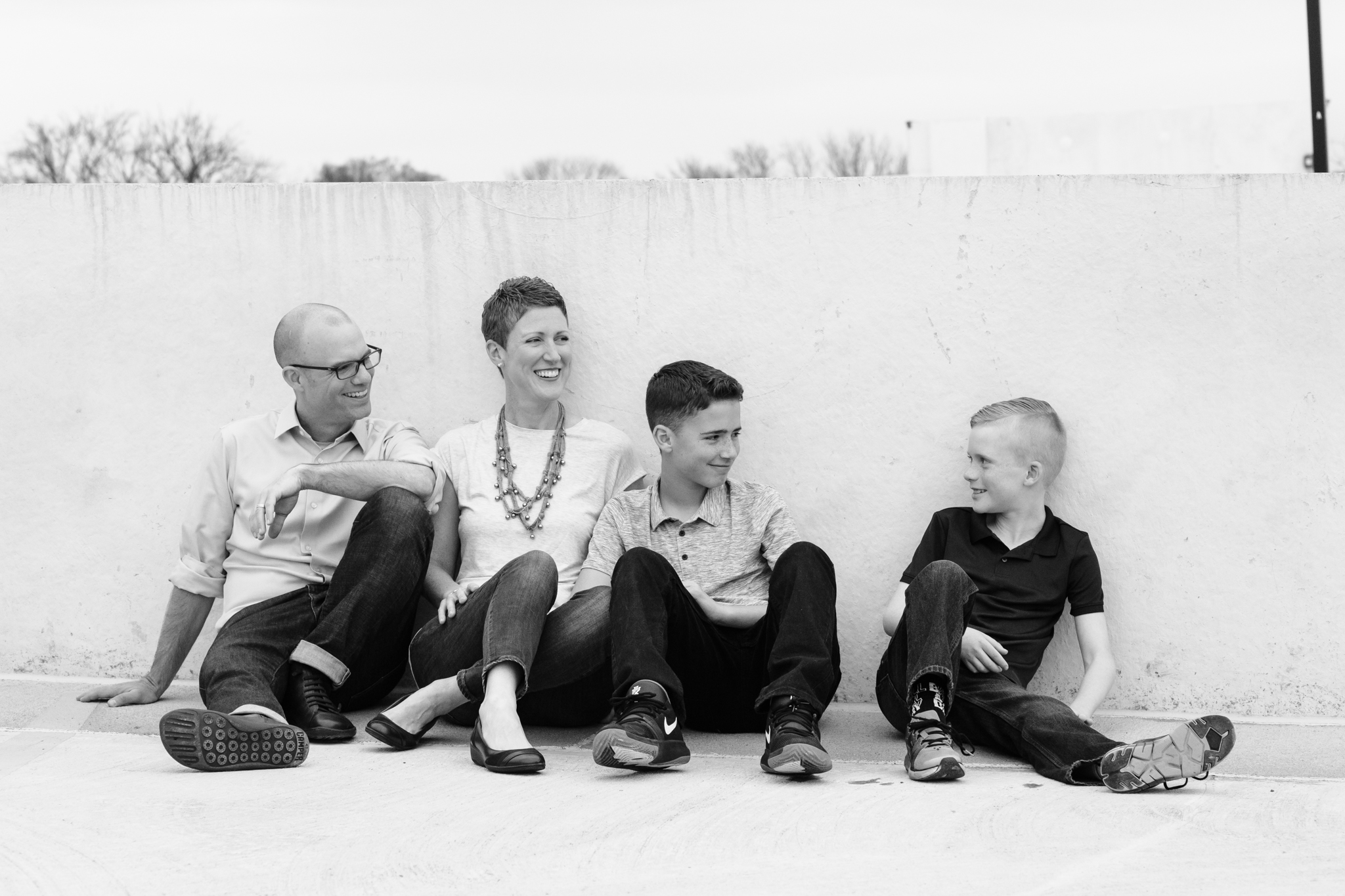 Black and White portrait of two parents and two pre-teen brother hang out on a rooftop